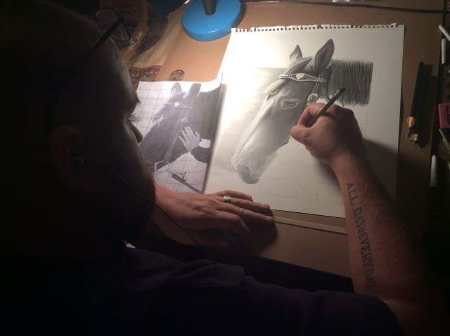 Drew Kasunik drawing a horse in pencil on commission.